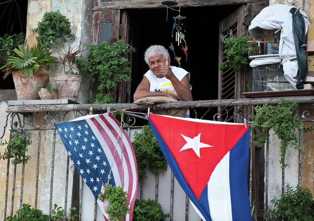 A Cuban gives the thumbs up from his balcony decorated with the US and Cuban flags in Havana.