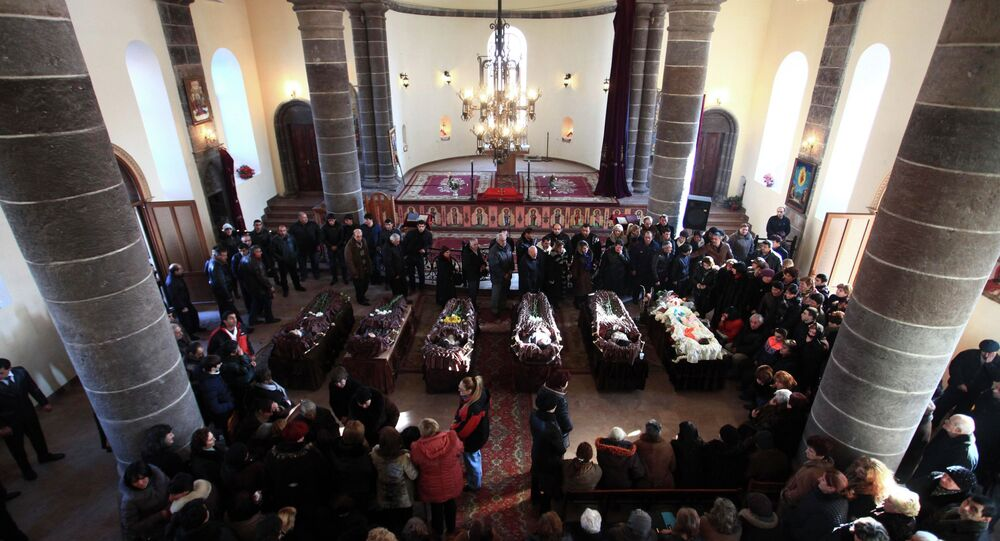 People surround coffins with the bodies of six murdered people during a funeral ceremony in Gyumri