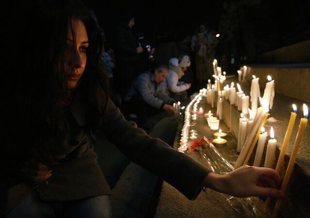 A woman lights a candle in the center of Yerevan on late January 13, 2015 in tribute to the six members of the same family allegedly killed by Russian soldier Valery Permyakov in the Armenian city of Gyumri