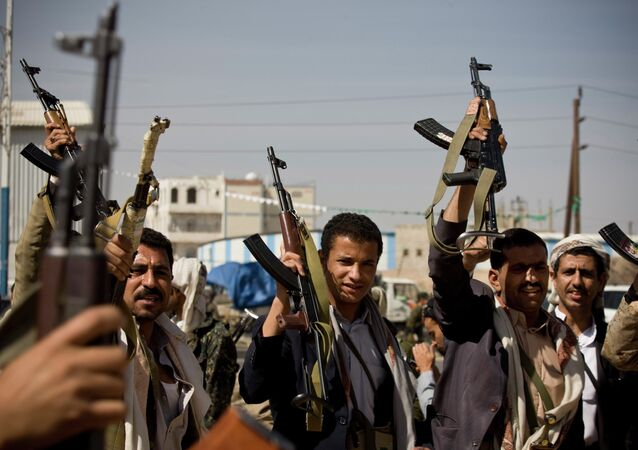 Houthi Shiite Yemeni hold their weapons