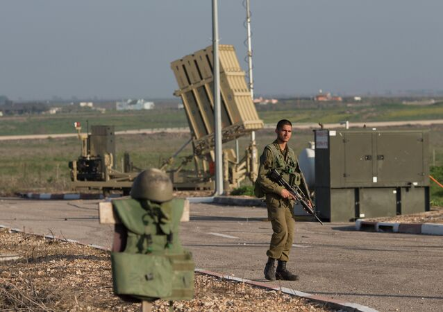An Israeli soldier guards an Iron Dome air defense system deployed in the Israeli controlled Golan Heights near the border with Syria, Tuesday, January 20, 2015.