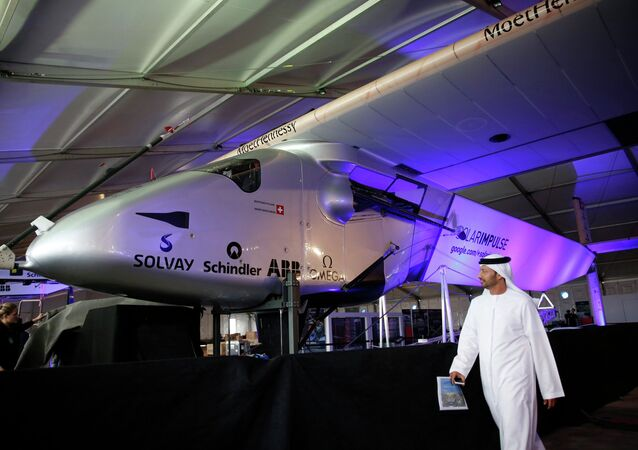 A man walks past the Solar Impulse 2 during its presentation at the Al Bateen airport in Abu Dhabi January 20, 2015.