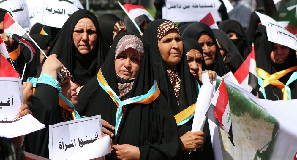 Iraqi women hold placards reading in Arabic: Help women who are abused by DAESH (Islamic State ) during a demonstration to denounce abuse against women by jihadists from the Islamic State