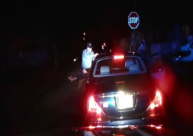 In this frame grab from an officer's dashboard camera taken Dec. 30, 2014, and provided by the Bridgeton, N..J. Police Department, police officers Braheme Days and Roger Worley stand near a car they pulled over for running a stop sign in Bridgeton