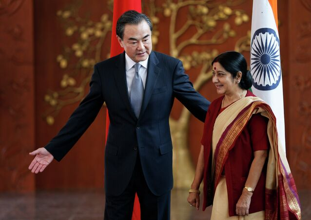 Indian External Affairs Minister Sushma Swaraj, right, and her Chinese counterpart, Wang Yi, leave for a meeting after a photo session in New Delhi, India, Sunday, June 8, 2014