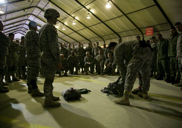 US Army soldiers of the 4th Infantry Brigade, Combat team (Airborne) 25th Infantry Division, part of the NATO-led peacekeeping mission in Kosovo listen to jump master how to prepare their gear for a parachute training exercise in US military base Camp Bondsteel, near the village of Sojeve in Kosovo on Sunday, Dec. 21, 2014