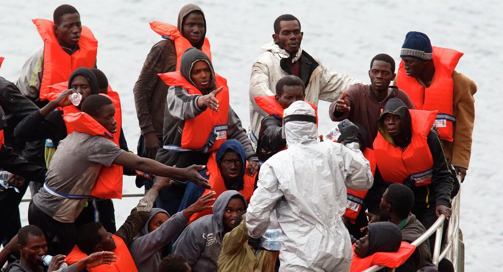 Rescued migrants on the deck of an Armed Forces of Malta (AFM) patrol boat reach out for bottles of water being distributed by a soldier in a biohazard suit after arriving at the AFM's Maritime Squadron base at Haywharf in Valletta's Marsamxett Harbour, January 22, 2015