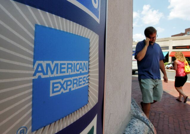 In this July 19, 2011 file photo, passers-by walk past an American Express logo near the entrance to a bank in the Harvard Square neighborhood of Cambridge, Mass