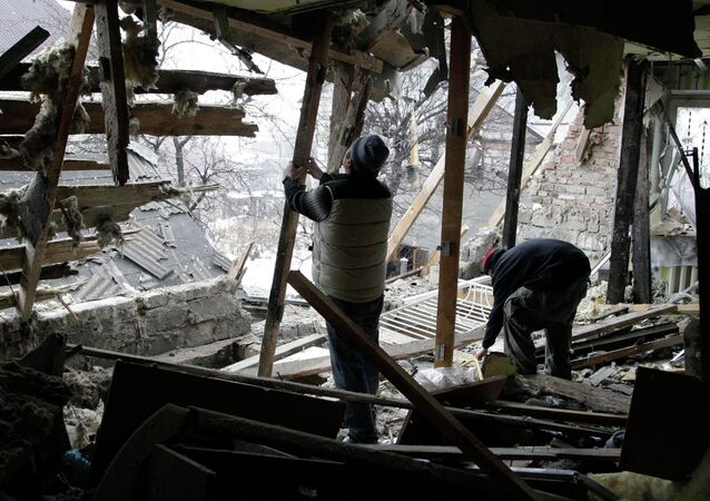 Local residents remove debris at a house damaged by recent shelling in Donetsk, eastern Ukraine, January 21, 2015