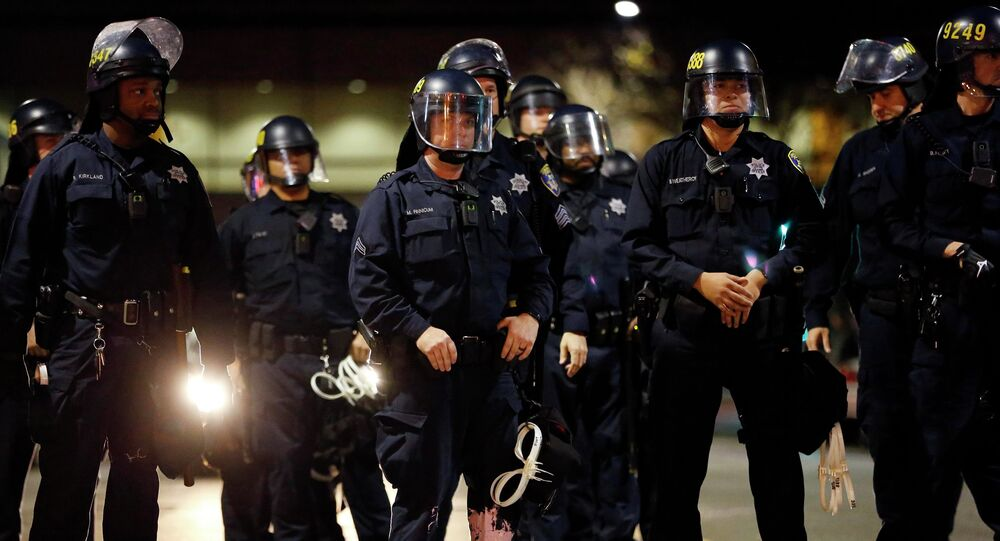 A police officer looks into the crowd, after he was hit on the leg with paint thrown by protesters during an evening demonstration against police violence, in Oakland, California December 13, 2014.