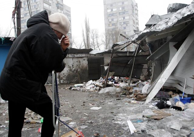 A woman reacts as she stands at a market, which according to locals was recently damaged by shelling, in Donetsk, eastern Ukraine January 19, 2015