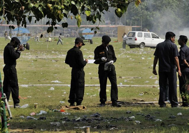Indian National Security Guard soldiers collect evidence from the site of bomb blasts at a central park in Bihar's state capital of Patna, India, Monday, Oct. 28, 2013