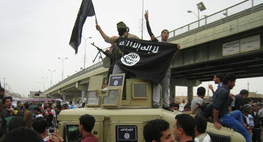 In this file photo, Islamic State group militants hold up their flag as they patrol in a commandeered Iraqi military vehicle in Fallujah, 40 miles (65 kilometers) west of Baghdad, Iraq