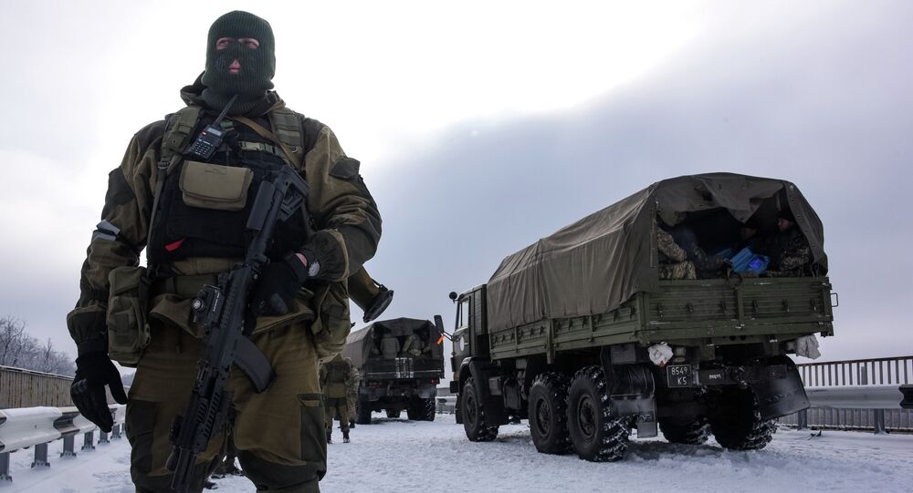A soldier guards the road near the airport of Donetsk, with Ukrainian military vehicles at rear, Eastern Ukraine, Tuesday, Jan. 6, 2015