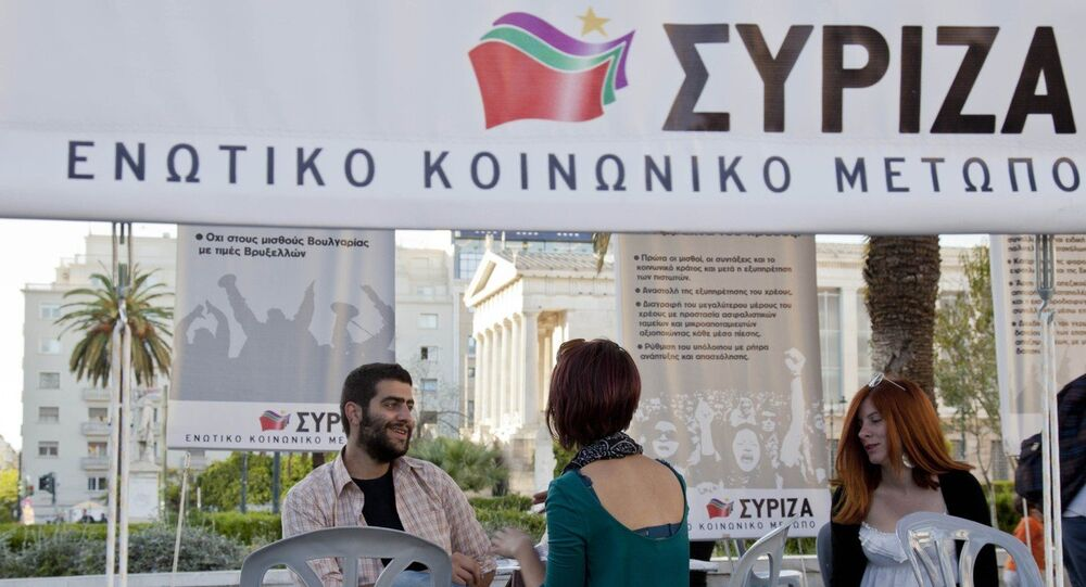 Young Greeks sit iat an election stand of the Radical Left Coalition (Syriza) downtown Athens.