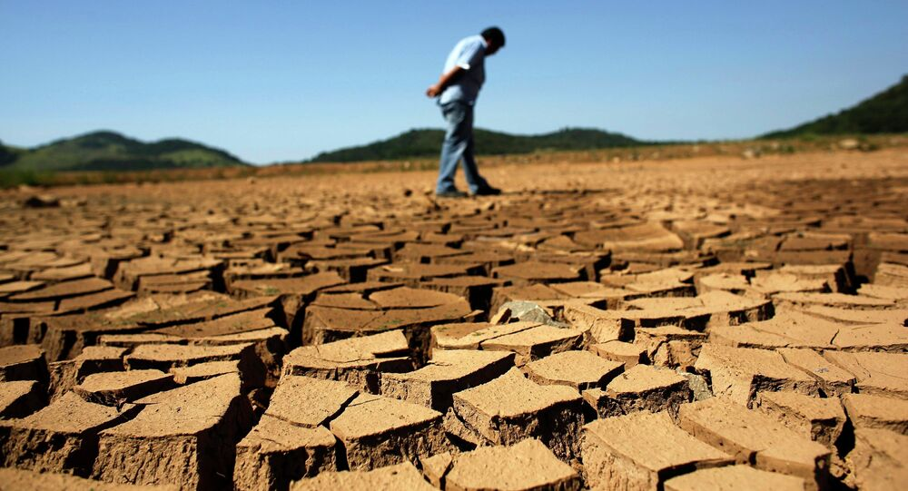 A worker from the Sao Paulo state company that provides water and sewage services to residential, commercial and industrial areas looks at the cracked ground of near Jaguary dam in Braganca Paulista, 100 km from Sao Paulo, in this file photo taken January 31, 2014