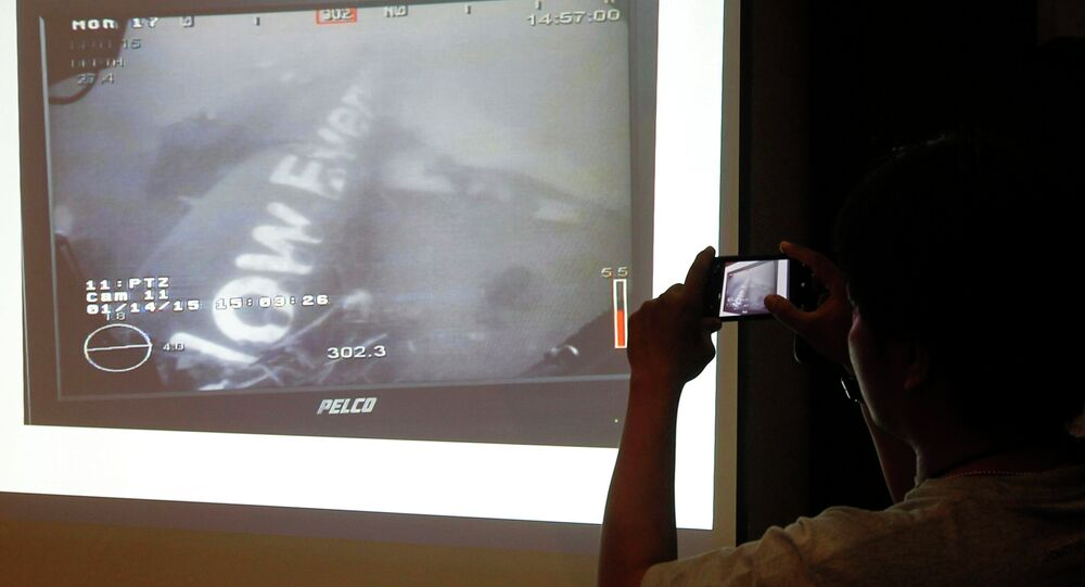 A journalist takes a photograph of an image believed to be of the fuselage of AirAsia Flight QZ8501