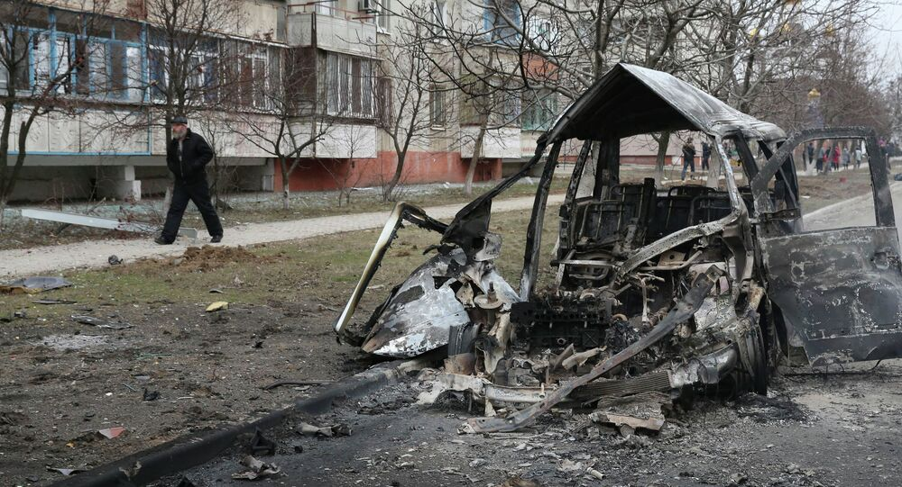 A man walks past a burnt-out vehicle after a shelling of a residential sector in Mariupol, eastern Ukraine, January 24, 2015