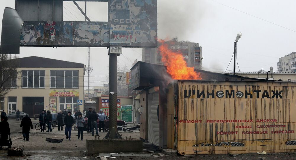 Peole look at a burning shop after shelling in the southern Ukrainian port city of Mariupol on 24, 2015