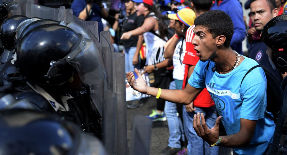 Opponents of Venezuelan President Nicolas Maduro demonstrate in front of riot police in Caracas on January 24, 2015