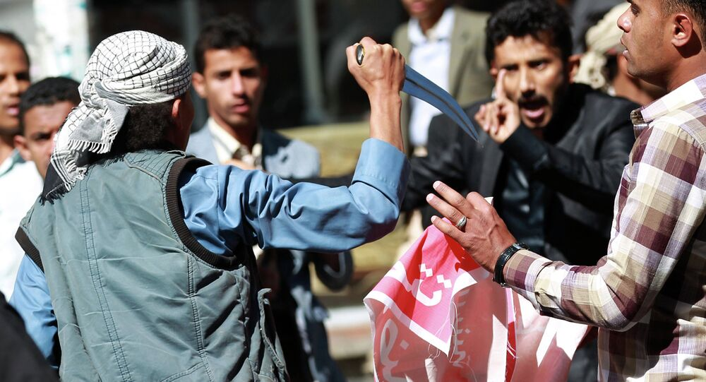 A Shiite Huthi rebel threatens Yemeni protesters during a rally against the control of the capital by Huthi rebels on January 24, 2015 in the capital Sanaa
