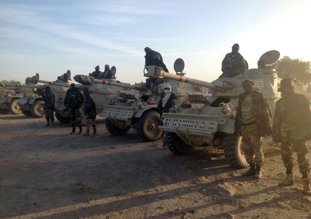 Soldiers of the Chadian army stand next to Panhard AML 90 armoured vehicles on January 21, 2015, at the border between Nigeria and Cameroon