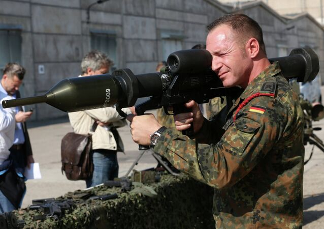 A member of the German army Bundeswehr presents a weapon which is part of a military aid for Iraq during a press event in Waren, northeastern Germany, Thursday, Sept. 18, 2014