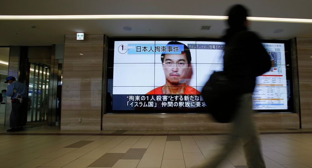 A man walks past screens displaying a television news programme showing an image of Kenji Goto, one of two Japanese citizens taken captive by Islamic State militants, on a street in Tokyo January 25, 2015