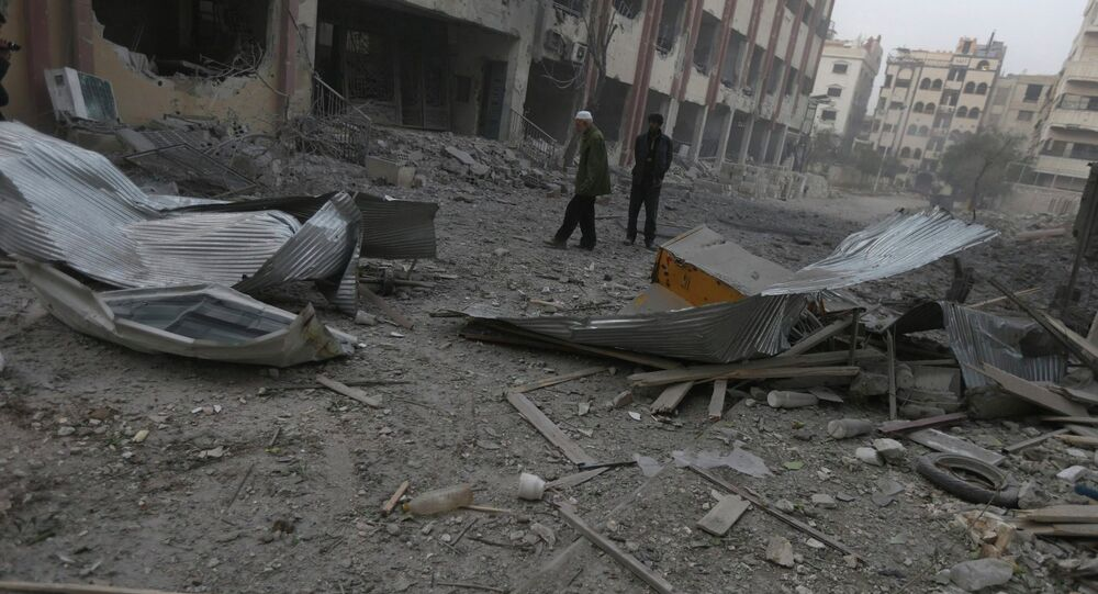Residents inspect a damaged site after what activists said were air strikes by forces loyal to Syria's President Bashar al-Assad in Douma eastern Al-Ghouta, near Damascus January 25, 2015