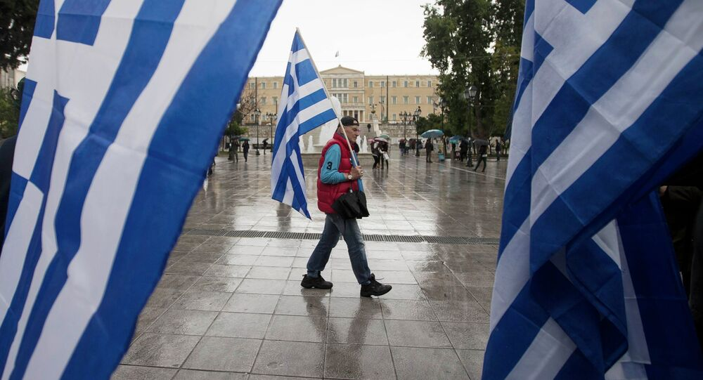 A man holding a Greek flag walks on central Syntagma square as the parliament is seen in the background, in Athens January 24, 2015