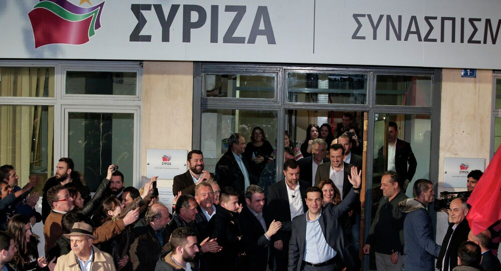 Leader of Syriza left-wing party Alexis Tsipras waves to supporters outside his party headquarters in Athens, Sunday, Jan. 25, 2015.