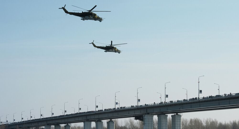 MI 24 helicopters fly at an air show as part of the Air Force Contract Service is Your Choice campaign near the river terminal over the embankment in Barnaul.