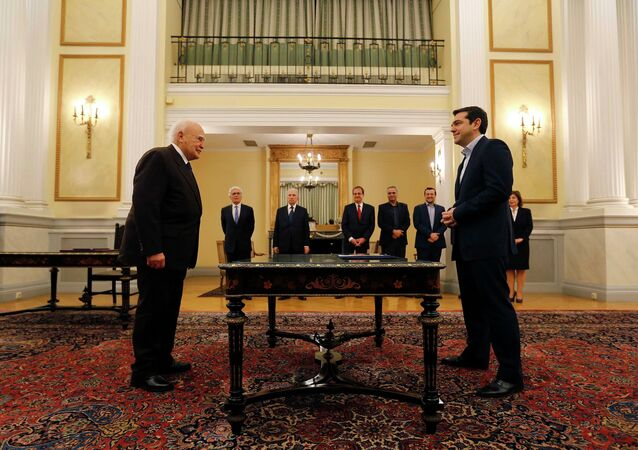 Head of radical leftist Syriza party and winner of the Greek parliamentary elections Alexis Tsipras (R) stands in front of Greek President Karolos Papoulias in the Presidential Palace in Athens during a swearing in ceremony as Greece's first leftist Prime Minister