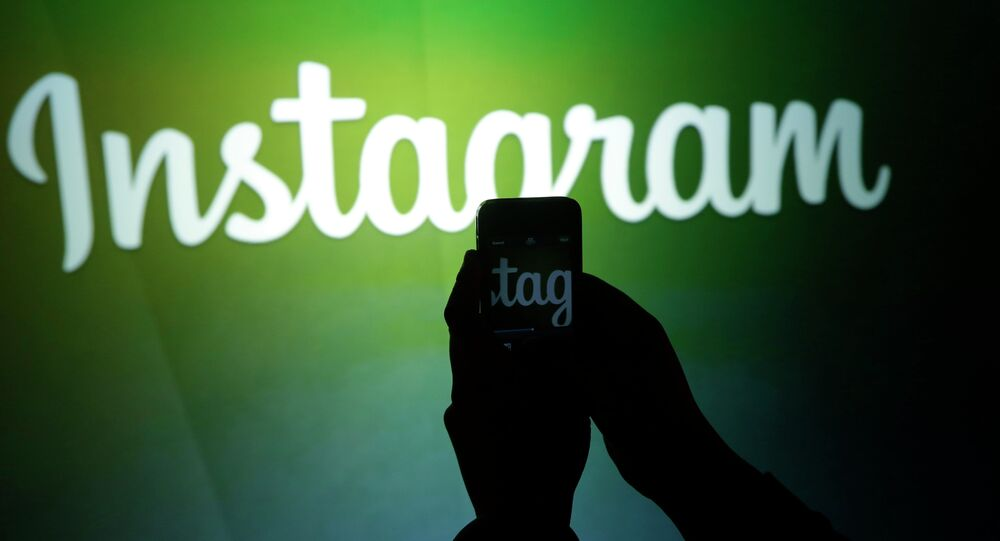 A journalist makes a video of the Instagram logo