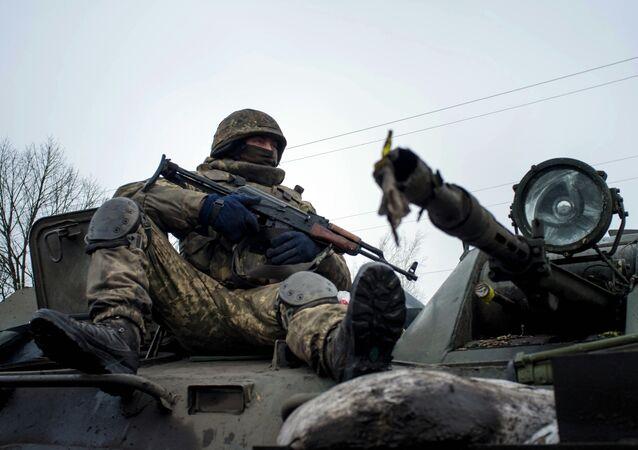A Ukrainian serviceman rides on APC
