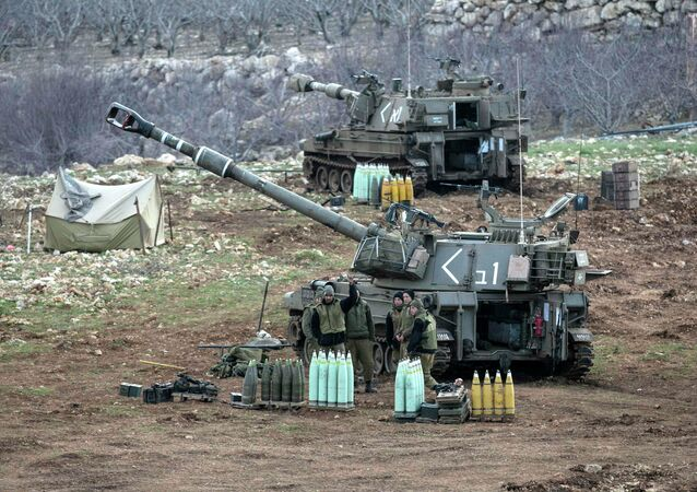 Israeli soldiers stand next to a mobile artillery unit near the border with Syria in the Golan Heights January 28, 2015