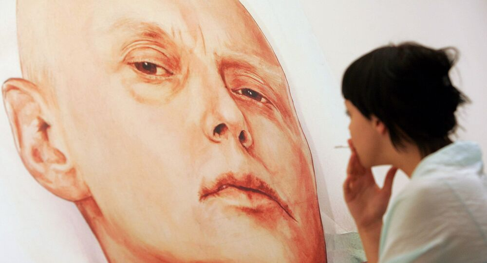An art gallery visitor looks at a painting showing Alexander Litvinenko