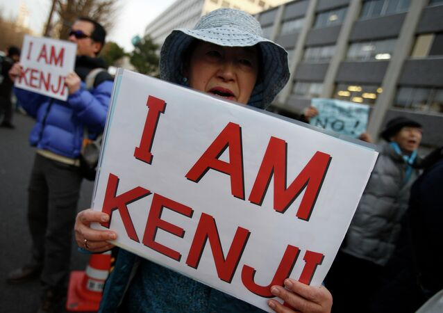 Protesters holding placards chant Save Kenji during a demonstration in front of the Prime Minister's Official residence in Tokyo
