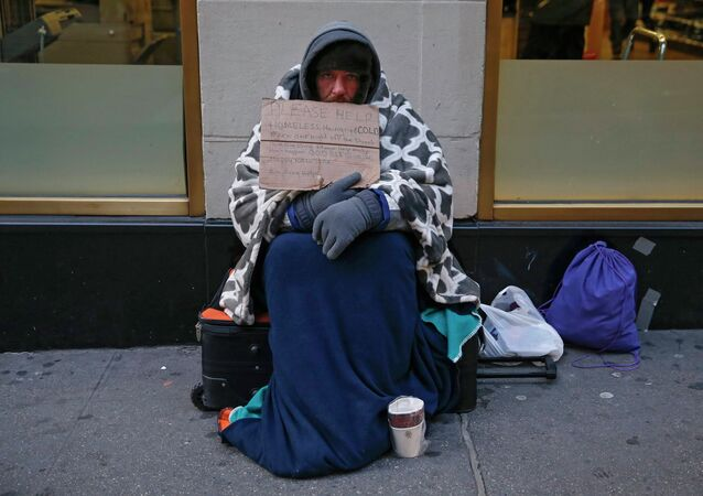 A man holding up a sign stating he is 'homeless, hungry and cold' sits along 7th avenue in New York