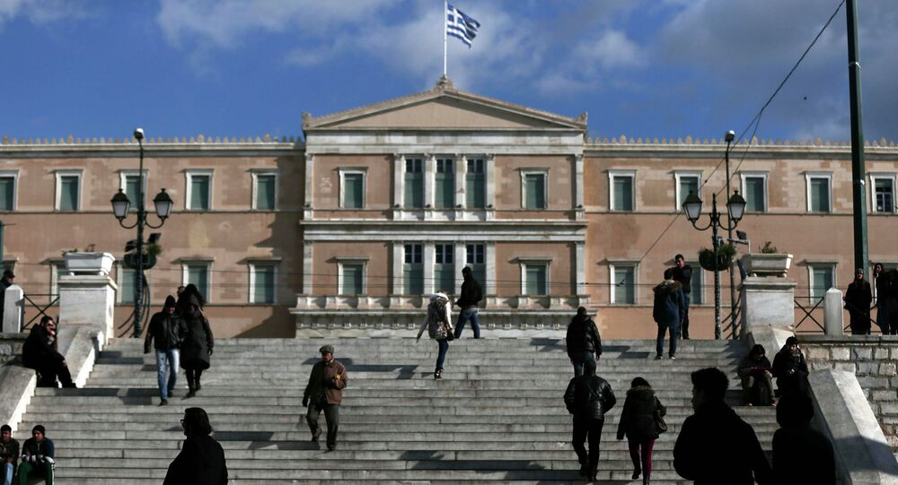 People make their way in central Syntagma Square as the parliament building is pictured in the background in Athens