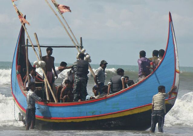 Rohingya refugees, who survived after their overloaded boat heading to Malaysia sank, are pictured on a fishing boat following their rescue by Bangladeshi border guards