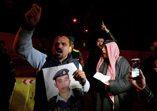 A relative of Islamic State captive Jordanian pilot Muath al-Kasaesbeh up his picture as they shout slogans demanding the Jordanian government negotiate with Islamic State for his release, in front of the Royal Palace in Amman January 28, 2015