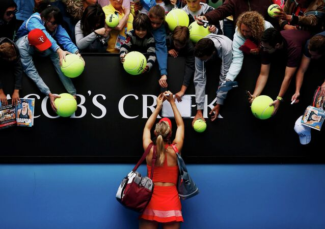 Maria Sharapova of Russia signs autographs after defeating Eugenie Bouchard of Canada in their women's singles quarter-final match at the Australian Open 2015 tennis tournament in Melbourne