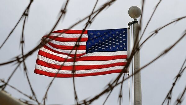 An American Flag is seen through razor wire at Camp VI in Camp Delta where detainees are housed at Naval Station Guantanamo Bay in Cuba - Sputnik International