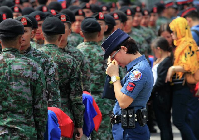 A policewoman wipes her tears as she stands in front of metal caskets containing the bodies of Special Action Force (SAF) police who were killed in Sunday's clash with Muslim rebels, at Villamor Air Base in Pasay city, metro Manila January 29, 2015