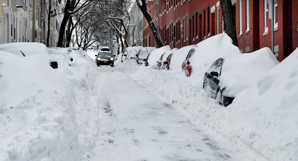 A car makes its way down a street filled with snowed-in vehicles in Boston's Charlestown section, Wednesday, Jan. 28, 2015 one day after a blizzard dumped about two feet of snow in the city