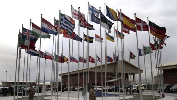 NATO Soldiers walk under country member flags at a NATO base at Kabul International Airport in Kabul, Afghanistan - Sputnik International