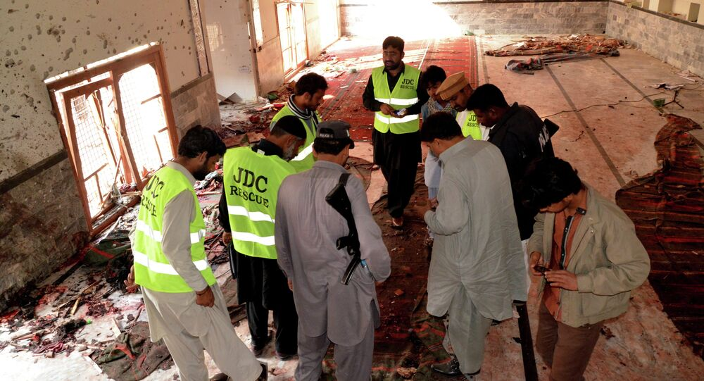 Pakistani investigators and security officials look for forensic evidence at a Shiite mosque in Shikarpur, Pakistan, Friday, Jan. 30, 2015.
