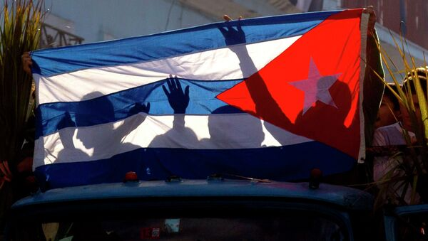 Children's shadows are cast on a Cuban national flag as they take part in a caravan tribute marking the 56th anniversary of the original street party that greeted a triumphant Castro and his rebel army, in Regla, Cuba, Thursday, Jan. 8, 2015 - Sputnik International