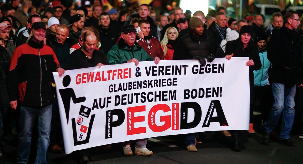 Participants hold a banner during a demonstration called by anti-immigration group PEGIDA